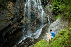 Jonge mens met een hond dichtbij een waterval stock afbeeldingen