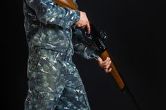 Jonge mens met een kanon Een militair in militaire eenvormig met een jachtgeweer Oorlogsspels Voorbereiding voor de lente, de her stock afbeeldingen