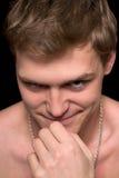Jonge mens met een kwaadwillige grijns Stock Afbeelding
