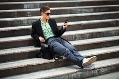 Jonge mens met een mobiele telefoonzitting op de stappen stock afbeelding