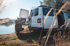 Jonge mens met een omgezette bestelwagen bij een meer in aard stock foto