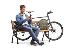 Jonge mens met een telefoon en een fietszitting op een houten bank Stock Foto