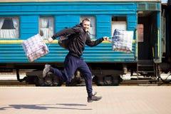 Jonge mens met grote die zakken bij station in werking worden gesteld stock foto
