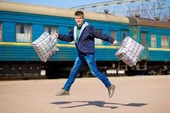 Jonge mens met grote die zakken bij station in werking worden gesteld Reis royalty-vrije stock foto