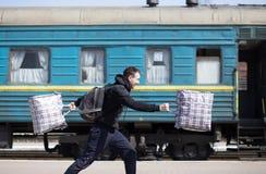 Jonge mens met grote die zakken bij station in werking worden gesteld Reis royalty-vrije stock fotografie