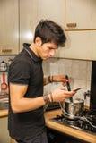 Jonge Mens met het Kokende Voedsel van de Celtelefoon op Fornuis Stock Foto's