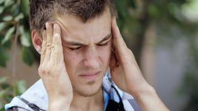 Jonge mens met hoofdpijn stock footage