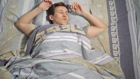 Jonge mens met hoofdpijnontwaken in bed thuis stock videobeelden