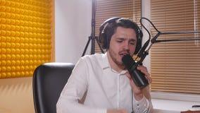 Jonge mens met hoofdtelefoons die op mic spreken Online radio en podcasting concept stock videobeelden