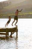 Jonge mens met kind het springen Stock Foto's