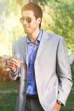 Jonge mens met kleding, zonnebril en cocktail ter beschikking In openlucht aperitivopartij Royalty-vrije Stock Afbeeldingen