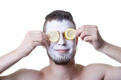 Jonge mens met kleimasker op zijn die gezicht, op wit wordt geïsoleerd stock foto's
