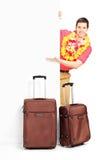 Jonge mens met koffers die achter paneel stellen Royalty-vrije Stock Foto