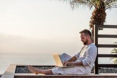 Jonge mens met laptop bij zonsondergang Stock Afbeelding