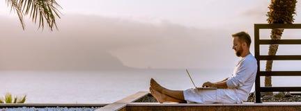 Jonge mens met laptop bij zonsondergang Royalty-vrije Stock Afbeeldingen