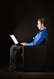 Jonge mens met laptop in dark royalty-vrije stock foto