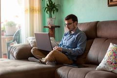 Jonge mens met laptop op bank thuis royalty-vrije stock foto