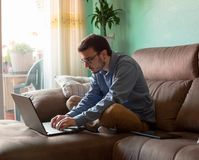 Jonge mens met laptop op bank thuis stock afbeelding