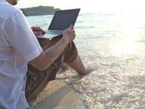 Jonge mens met laptop zitting op zand van tropisch strand tijdens zonsondergangtijd Ontspan en reis concept royalty-vrije stock foto's