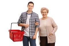 Jonge mens met lege het winkelen mand en bejaarde stock fotografie