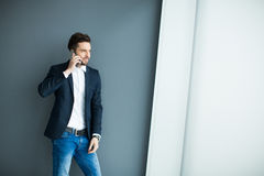 Jonge mens met mobiele telefoon door de muur Royalty-vrije Stock Foto's