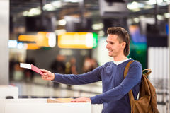 Jonge mens met paspoorten en het inschepen kaartjes bij stock afbeelding