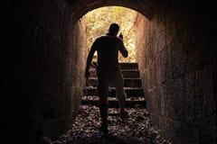 Jonge mens met radio die in donkere steentunnel wordt geplaatst Stock Foto's
