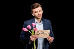 Jonge mens met roze tulpen en droevig teken die hopelijk camera bekijken stock foto