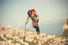Jonge Mens met rugzak en trekkingspolen openlucht lopen Royalty-vrije Stock Afbeelding