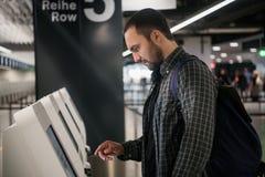 Jonge mens met rugzak wat betreft interactieve vertoning die zelfbedieningsmachine met behulp van, die zelf-controle-binnen voor  stock afbeelding