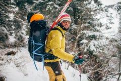 Jonge mens met ski die zich in het sneeuwbos bevinden Royalty-vrije Stock Afbeeldingen