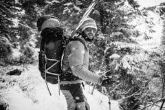 Jonge mens met ski die zich in het sneeuwbos bevinden Royalty-vrije Stock Afbeelding