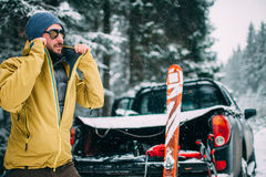 Jonge mens met ski in het sneeuwbos Stock Foto