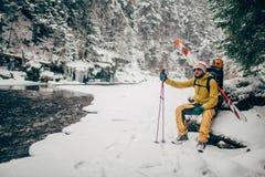 Jonge mens met skizitting in het sneeuwbos Stock Afbeeldingen