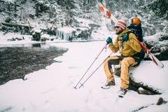 Jonge mens met skizitting in het sneeuwbos Stock Foto