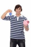 Jonge mens met sleutel en piggybank. Royalty-vrije Stock Afbeeldingen