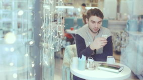 Jonge mens met smartphonezitting in koffie stock videobeelden