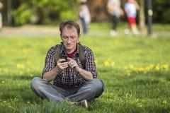 Jonge mens met smartphonezitting op het gras in een stadspark Royalty-vrije Stock Fotografie
