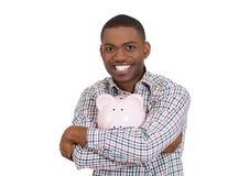 Jonge mens met spaarvarken gelukkig over zijn besparingen Stock Foto's