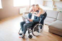 Jonge mens met speciale behoeften Het zitten op rolstoel en het spreken op telefoon De jonge vrouw omhelst hem Erachter status va stock afbeelding