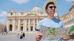 Jonge mens met stadskaart in de stad van Vatikaan en St Peter Basiliekkerk, Rome, Italië De mens van de reistoerist met kaart stock footage