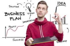 Jonge mens met tekeningsstootkussen en pen die businessplan veronderstellen royalty-vrije illustratie