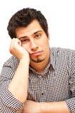 Jonge mens met vermoeide, onverschillige uitdrukking Stock Foto