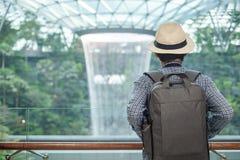 Jonge mens met zak en hoed, Aziatische reiziger die en zich aan mooie regendraaikolk Juweelchangi Luchthaven, oriëntatiepunt bevi royalty-vrije stock fotografie