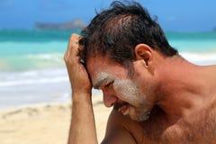 Jonge mens met zand op gezicht door strand Stock Foto