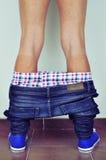 Jonge mens met zijn die broek neer erachter wordt gezien van Stock Foto's