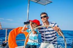 Jonge mens met zijn zoons varend jacht Royalty-vrije Stock Foto