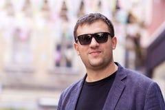 Jonge mens met zwarte zonnebril en jasje op de straat Royalty-vrije Stock Foto's