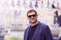 Jonge mens met zwarte zonnebril en jasje op de straat Royalty-vrije Stock Foto