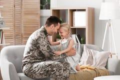 Jonge mens in militaire eenvormig met zijn kleine dochter Royalty-vrije Stock Foto's